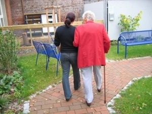 Caregiver walking elderly woman with cane on path, Alzheimer's with agitation, clinical research